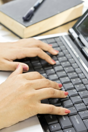 Womans hands on a notebook keyboard close up - typing  Stock Photo