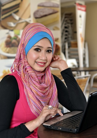 muslim girl: Pretty Muslim girl with laptop at cafe  Stock Photo