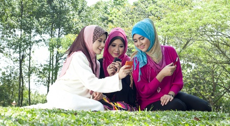 malay ethnicity: Beautiful young Muslim women having fun with their phone  Stock Photo