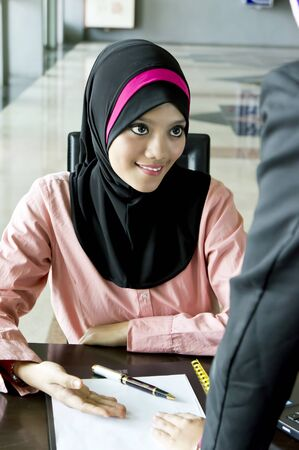 Portrait of a young Muslim secretary explain about something photo