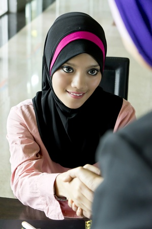 Portrait of a young Muslim manager shaking the hand of a customer photo