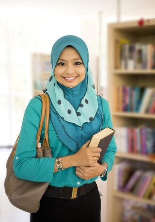 Beautiful young muslim girl in library