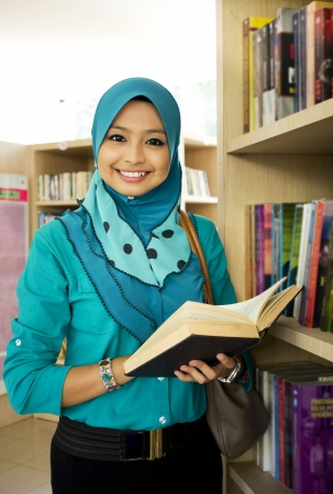 pretty young muslim girl study at library photo