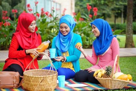 malay food: Three young Muslim girl picnic at park