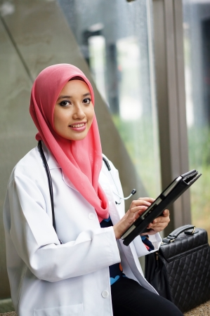 Young asian Muslim woman doctor in head scarf smile with tablet device Stock Photo