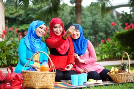 femmes muslim: Belles jeunes filles musulmanes Prendre une photo avec le t�l�phone � la main au parc avec le visage heureux Banque d'images