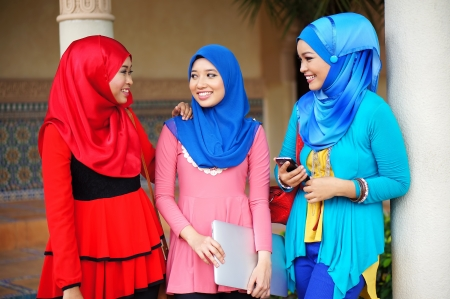 Three beautiful muslim girls having fun talking each other