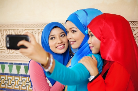 Beautiful young Muslim girl taking photo with smart phone