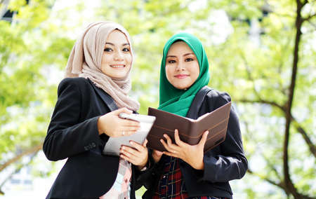 two young muslim woman have discussion at park looking to camera photo
