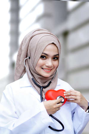 A young doctor woman holding a heart symbol photo
