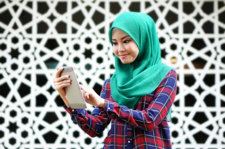 young muslim woman using tablet phone in front of islamic background photo