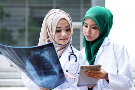 beautiful young muslimah doctors discussing about xray result photo