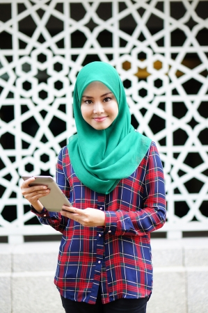 beautiful young muslimah holding tablet in front of islamic background          photo