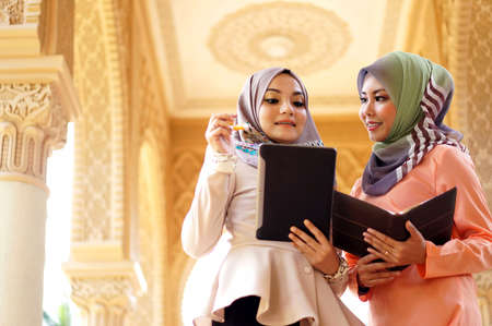 two pretty young muslimah student discussing about their study in islamic campus                                photo