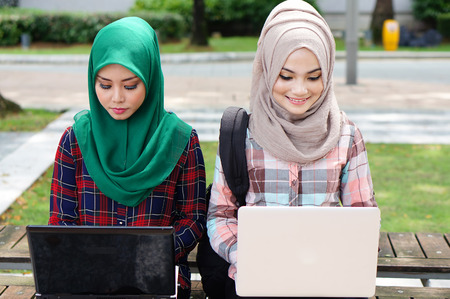 two beautiful muslim girl study together with laptop at the universiy park photo