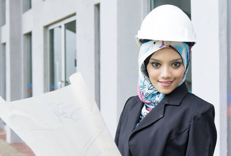Young female construction specialist with a blueprints photo