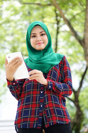 Beautiful young lady with tablet computer in the garden photo