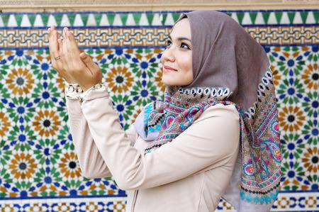 Beautiful muslim woman praying beside the islamic background photo