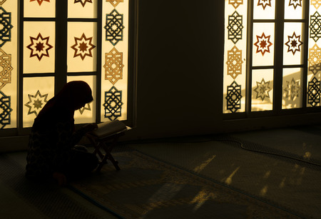 muslim: muslim woman reading Koran in the evening at Mosque Stock Photo