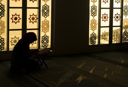 koran: muslim woman reading Koran in the evening at Mosque Stock Photo