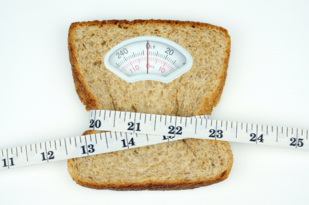 tapeline: Weight scale with wholesome slice of bread and measuring tape on white background