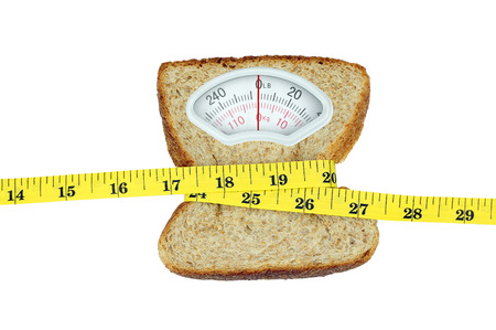 weight control: Weight scale with wholesome slice of bread and measuring tape on white background