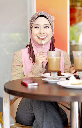 Muslim girl in head scarf using phone at cafe
