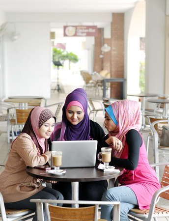 malay ethnicity: Beautiful Muslim girls using laptop at cafe Stock Photo
