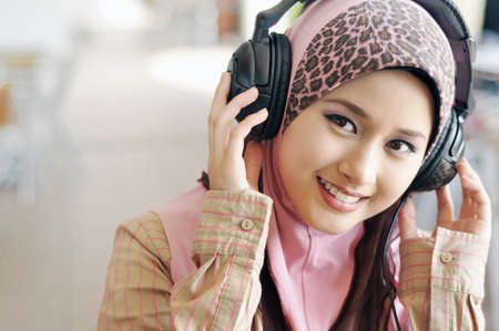 Beautiful Muslim girl enjoying listening to music photo