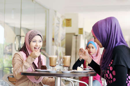 Beautiful Muslim girls chatting at cafe photo