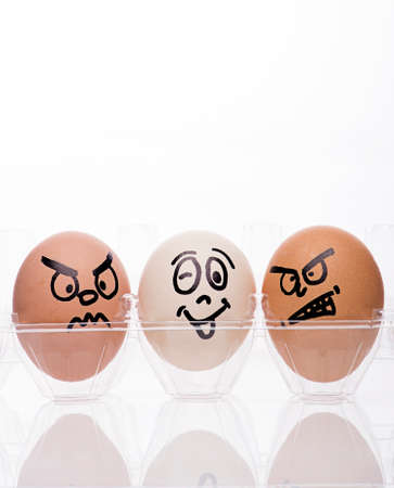 faces happy to sad: two egg characters displaying angry emotions towards a single white egg