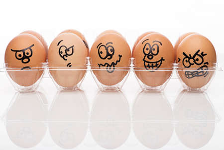 Funny faces on painted on brown eggs over white background photo