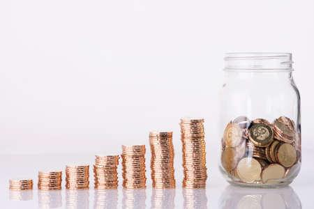 Image de pièces de monnaie d'or empilés et penny pot sur fond blanc Banque d'images