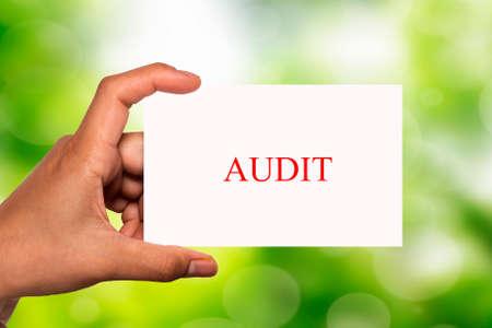 validity: mano que sostiene la tarjeta blanca de auditor�a por escrito sobre el fondo de desenfoque Foto de archivo