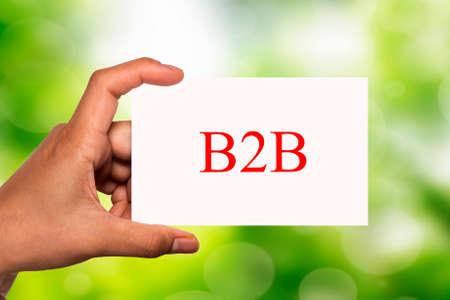 b2b: hand holding white card written B2B over blur background Foto de archivo
