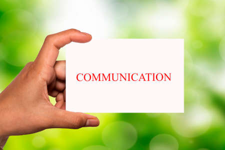 written communication: hand holding white card written communication over blur background Stock Photo