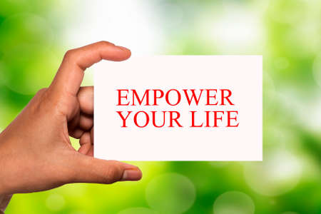 hand holding white card written empowerment over blur background