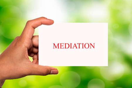 mediation: hand holding white card written mediation over blur background