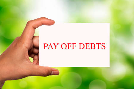 pay off: hand holding white card written pay off debts over blur background