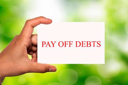 show bill: mano que sostiene la tarjeta blanca escrita pagar las deudas sobre fondo borroso
