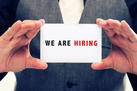 young executive holding card written we are hiring
