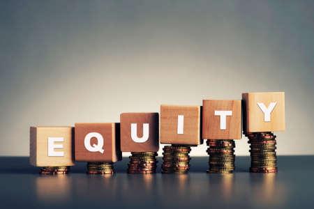 equity tekst geschreven op een houten blok met gestapelde munten op een grijze achtergrond Stockfoto
