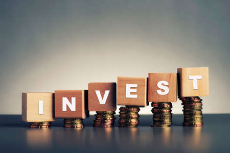business funds: invest text written on wooden block with stacked coins on grey background