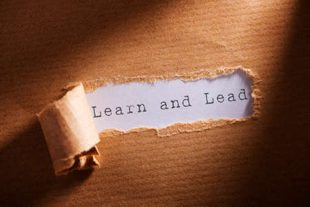 learn and lead: ripped paper with word learn and lead