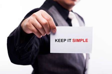 cogent: young executive holding card written keep it simple Stock Photo