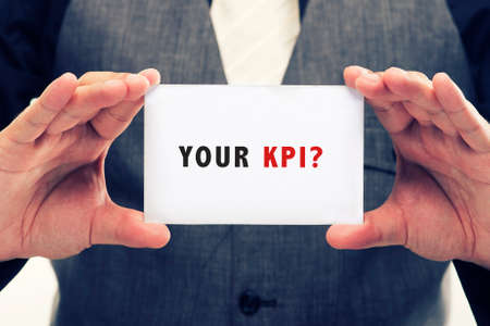 business concepts: young executive holding card written KPI