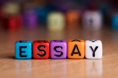 essay: essay words with dices on wooden table