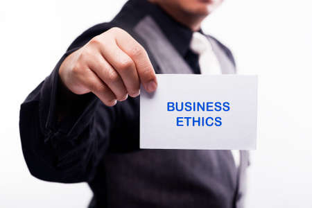 working ethic: young executive holding card written business ethics