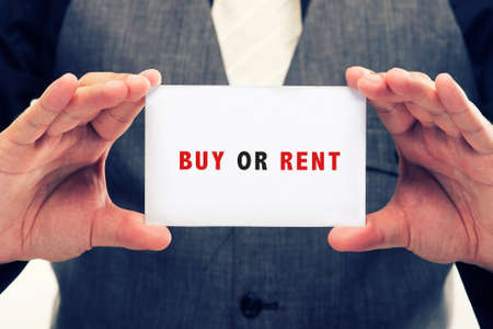 buying questions: Executive Holding card with Message Saying-Buy or rent Stock Photo