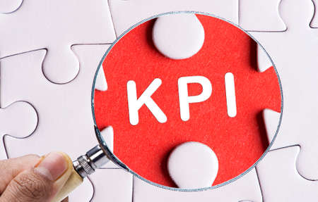 kpi: Magnifying glass searching missing puzzle peace KPI